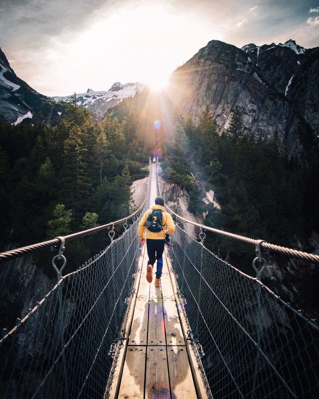 A man runs down a wooden bridge with mountains and sunshine gleaming in the distance. Photo by Fabio Comparelli on Unsplash.